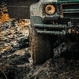 4x4 travel trekking. Offroad vehicle coming out of a mud hole hazard. Off-road travel on mountain road. Expedition. Offroader. Road adventure. Adventure travel stock photos