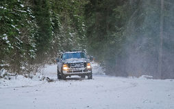 4x4 truck on winter snow road in forest. 4-wheel drive truck in a forest on a snowy road Royalty Free Stock Images