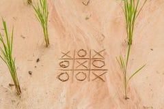 X und O-Spiel auf dem Sand Stockbild