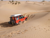 4X4 vehicle drives around the sand dunes of the Sahara Desert. SAHARA DESERT, TUNISIA - OCTOBER 12 - 4X4 vehicles navigate the dunes of the Sahara as part of a Stock Photo