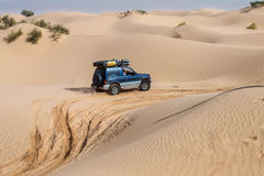 4X4 vehicle drives around the sand dunes of the Sahara Desert. SAHARA DESERT, TUNISIA - OCTOBER 12 - 4X4 vehicles navigate the dunes of the Sahara as part of a Royalty Free Stock Image