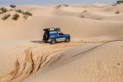 4X4 vehicle drives around the sand dunes of the Sahara Desert. Royalty Free Stock Image