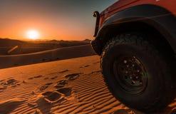 4x4 voertuig, woestijn en zonsondergang stock fotografie
