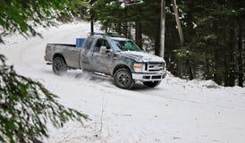 4x4 vrachtwagen die op de weg van de de wintersneeuw in bos afdrijven Stock Foto's