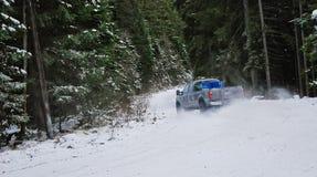 4x4 vrachtwagen die op de weg van de de wintersneeuw in bos afdrijven royalty-vrije stock foto's