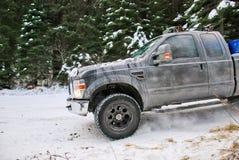 4x4 vrachtwagen die op de weg van de de wintersneeuw in bos afdrijven Stock Foto