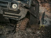 4x4 or 4WD car with wheels in mud. In the forest, off road. Car stuck in puddle of mud. Wheel covered with dirt. Extreme entertainment concept royalty free stock photo