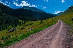 4x4 weg vom Straßenfahrzeugschotterweg, der herauf die Berge vorangeht Lizenzfreies Stockbild