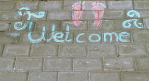 'Welcome' written on the sidewalk- great as background. 'Welcome' written on the sidewalk with light blue chalk, pink feet drawn next to it Royalty Free Stock Photography