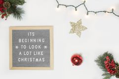 It's Beginning to Look a Lot Like Christmas Board Decor Beside Star and Red Bauble Flatlay Photography royalty free stock photography