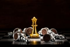 Xadrez da rainha do ouro cercada por um número de xadrez de prata caída p fotografia de stock royalty free