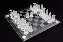 Xadrez de vidro em um fundo preto O começo do partido imagens de stock