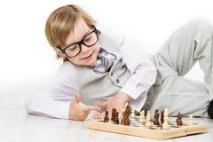 Xadrez do jogo de criança, menino esperto da criança no jogo dos vidros do terno de negócio fotografia de stock royalty free