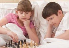 Xadrez do jogo de crianças em uma cama Foto de Stock