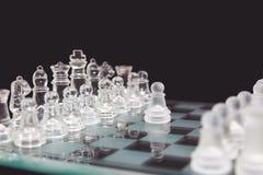 Xadrez do vidro em um fundo preto, o começo do jogo foto de stock royalty free