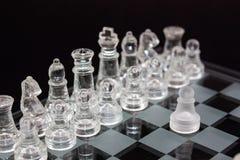 Xadrez do vidro em um fundo preto, o primeiro movimento do jogo fotografia de stock royalty free