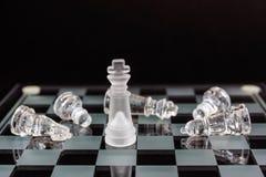 Xadrez do vidro O rei e derrotado o ` s do oponente remenda em um fundo preto fotos de stock