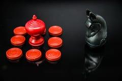 Xadrez vermelha do rei no grupo de desafio dos penhores com parte de xadrez de Thai do cavaleiro preto no fundo preto e no foco s Imagem de Stock