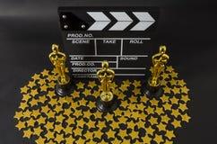 Plastic Oscar awards, a clapboard and golden stars confetti. XALAPA, VERACRUZ, MEXICO- FEBRUARY 14, 2019: Plastic Oscar awards, a clapboard and golden stars royalty free stock images