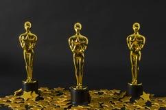 Plastic Oscar awards and golden stars confetti. XALAPA, VERACRUZ, MEXICO- FEBRUARY 14, 2019: Plastic Oscar awards and golden stars confetti against black royalty free stock photo