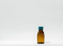 Xarope da medicina na garrafa ambarina com etiqueta e a colher de chá vazias Imagem de Stock Royalty Free