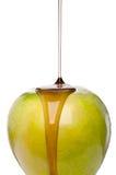 Xarope de bordo que está sendo derramado em uma maçã verde Fotos de Stock Royalty Free