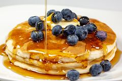 Xarope de derramamento sobre a manteiga na pilha do mirtilo de panquecas na mesa de cozinha que espera para ser comido imagens de stock royalty free