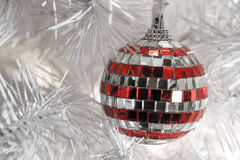 Xballstr. Red and white striped mirrored mosaic Christmas ornament hanging from branch of modern white  artificial tree Royalty Free Stock Image