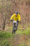 XC rider in yellow suit. XC rider moves through narrow part of trail. Cross-country cycling trail in Odessa, Ukraine Stock Photos