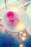 Xícara de café e luzes de Natal mornas em uma tabela Fotos de Stock