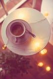 Xícara de café e luzes de Natal mornas em uma tabela Imagem de Stock Royalty Free