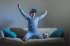年轻人xcited使用VR虚拟现实风镜头饰的游戏玩家人打橄榄球在家庆祝计分的目标的模仿计划 图库摄影