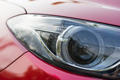 Xenon projector headlight of a red car Royalty Free Stock Photo