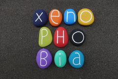 Xenophobia, social issue concept word composed with colored stones over black volcanic sand. Xenophobia text composed with multi colored sea stones over natural stock images