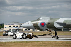 XH558 on tow. FARNBOROUGH AIRSHOW, UK - JULY 24, 2010: Avro Vulcan XH558 towed by an airfield tug truck due to brake failure Royalty Free Stock Images