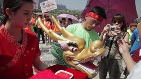 XI '- JUN 12: De mensen verfraaien hoofd van draak vóór het traditionele ras van de draakboot tijdens Dragon Boat Festival, Jun 1 stock footage