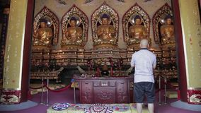 XI`AN CHINA - MAY 27 2012: Buddhists pray inside the Temple stock video footage
