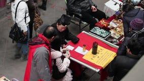 XI ?UMA CHINA - 6 DE FEVEREIRO DE 2012: O adivinho diz fortunas para uma menina no mercado vídeos de arquivo
