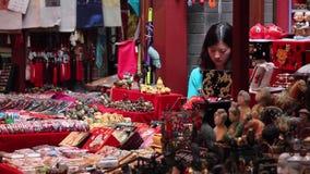 Xian, Китай - 26-ое мая 2012: Неопознанные люди выбирают традиционные сувениры на стойле на торговой улице в Xian сток-видео