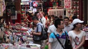 Xian, China - 26 de mayo de 2012: La gente no identificada elige recuerdos tradicionales en la parada en la calle que hace compra almacen de video