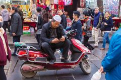 Chinese Muslim man sits on his motorcycle using his phone on the. XIAN, CHINA - 10 March 2018 - Chinese Muslim man sits on his motorcycle using his phone on the royalty free stock photography