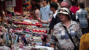 XIAN, CHINA - MAY 26, 2012: Unidentified people choose traditional souvenirs at the stall at the shopping street in Xian stock video footage