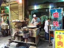 Market vendors at street of Xian offer their customers various types of ravioli. XIAN, CHINA - OCTOBER 17, 2013: Market vendors at street of Xian offer their stock image