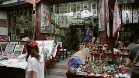 Xian, Cina - 26 maggio 2012: La gente non identificata sceglie i ricordi tradizionali alla stalla alla strada dei negozi in Xian stock footage