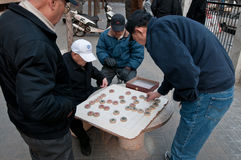 Xiangqi. Beijing, China - March 30th, 2013: Chinese men playing Chinese chess called Xiangqi on street in Beijing Royalty Free Stock Photos