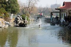 Xiaoyaojin Park Hefei China. A water fountain and Chinese people fishing in the waters of Xiaoyaojin park in Hefei China located in Anhui Province Royalty Free Stock Images