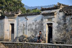 XIDI, ANHUI PROVINCE, CHINA – CIRCA OCTOBER 2017: A man sitting in front of his house in Xidi. Xidi was declared a part of the `Ancient Villages in royalty free stock images