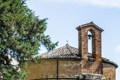 XIII century baptistery church with brick wall and small bell Stock Photos