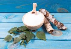 Xilitol - substituto del azúcar Azúcar del abedul en fondo de madera azul Fotos de archivo