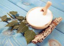 Xilitol - substituto del azúcar Azúcar del abedul en fondo de madera azul Imagen de archivo libre de regalías